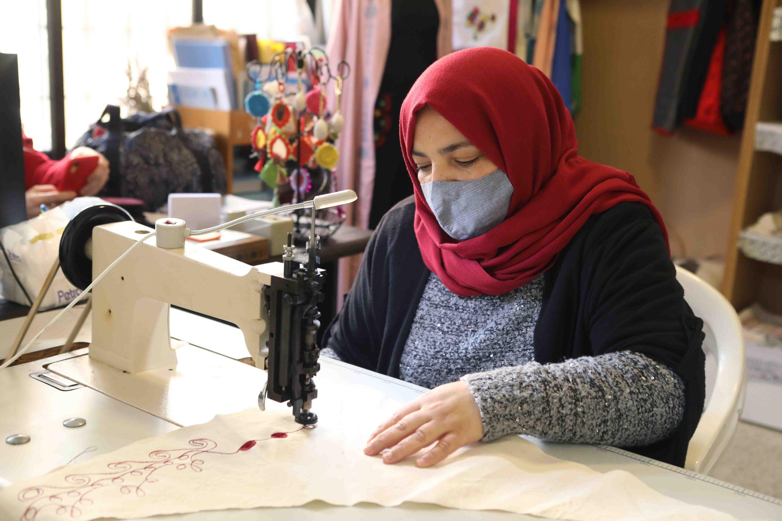 Una mujer con una mascarilla usa una máquina de coser