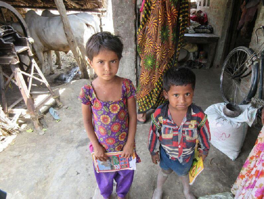 Two young children, a girl and a boy, hold books in their hands.