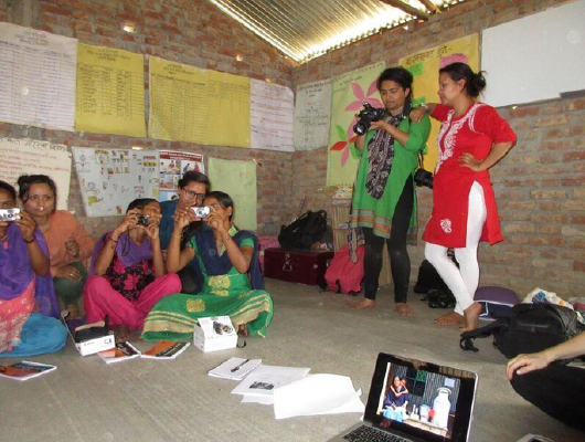 Women in a brick house, some seating and others standing, are holding cameras.