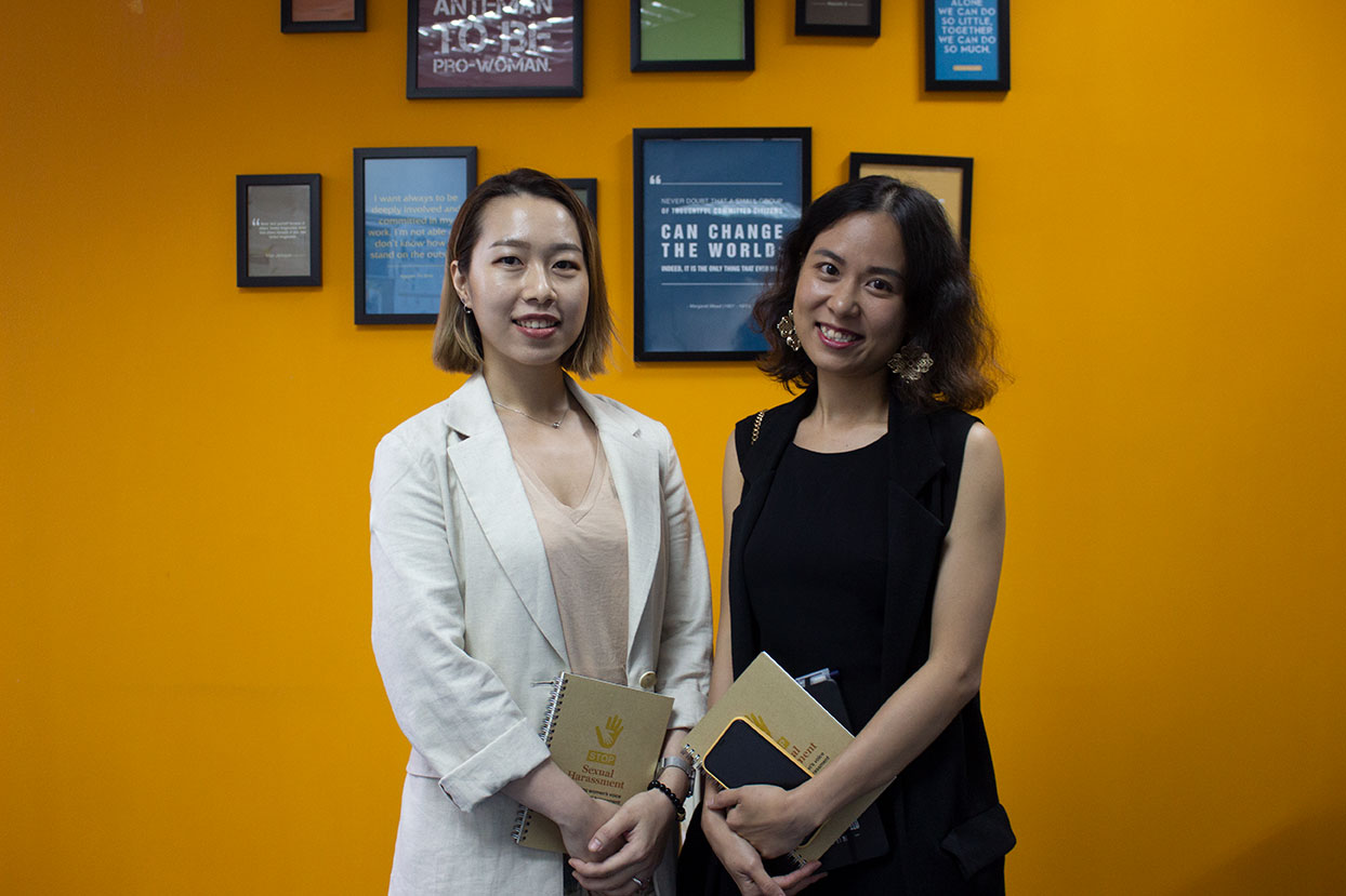 Two women, Nguyen Thanh Tra and Trang, stand next to each other in front of a mustard yellow wall full of framed photos.