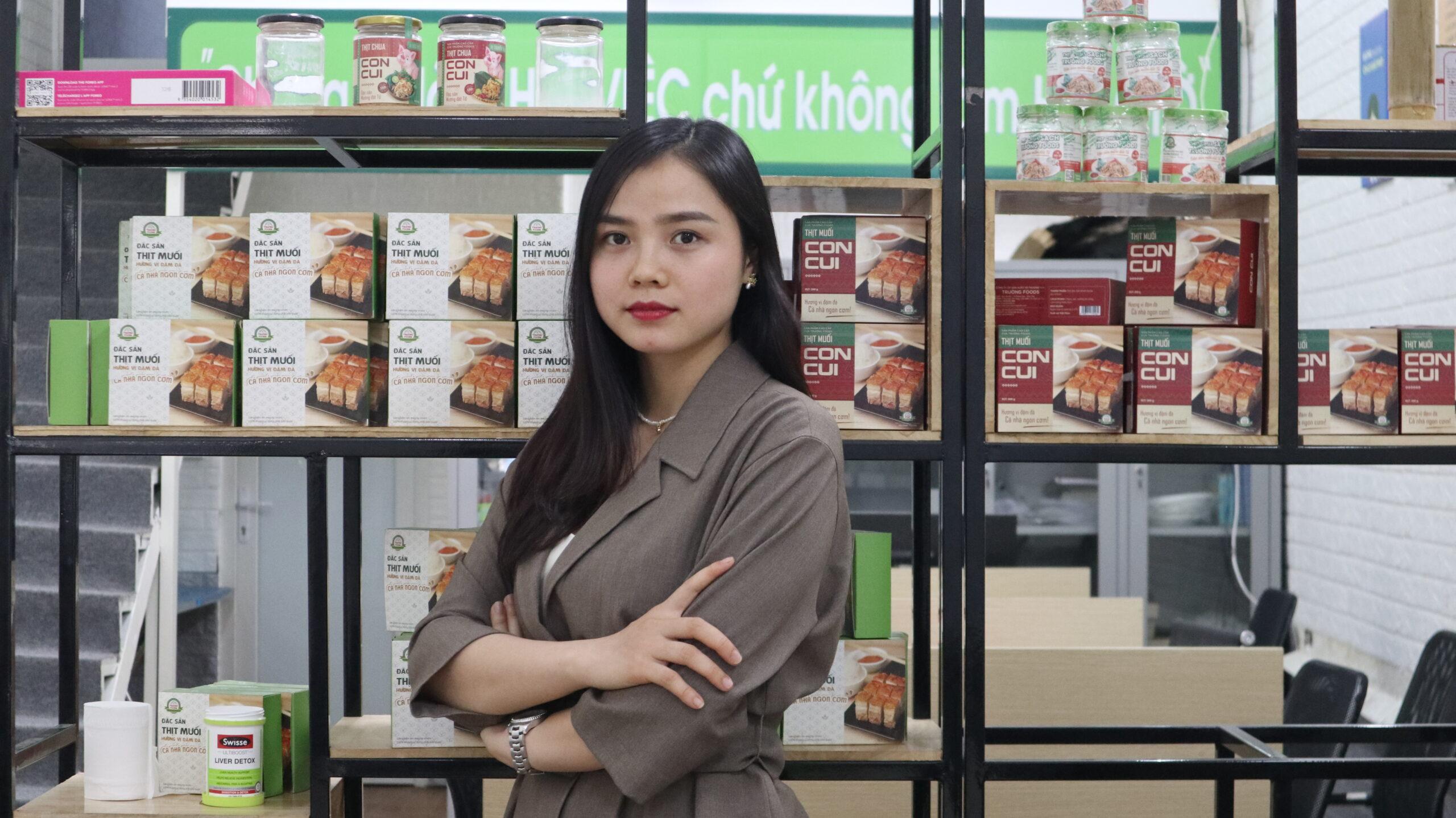 Uma mulher está diante de prateleiras repletas de comida.