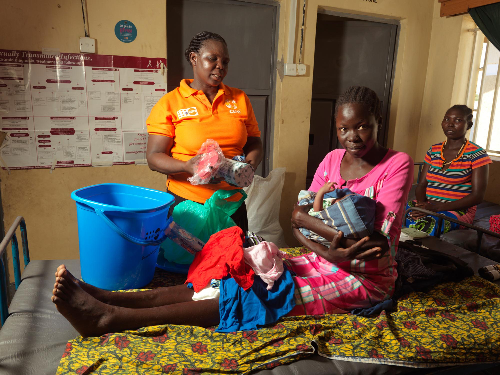 Uma mulher está sentada em uma cama com um bebê nos braços. Outra mulher se senta em uma cadeira enquanto um funcionário da CARE fica de pé.