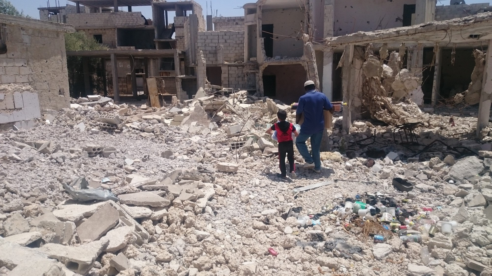 A man and a child walk through the rubble of a destroyed building.