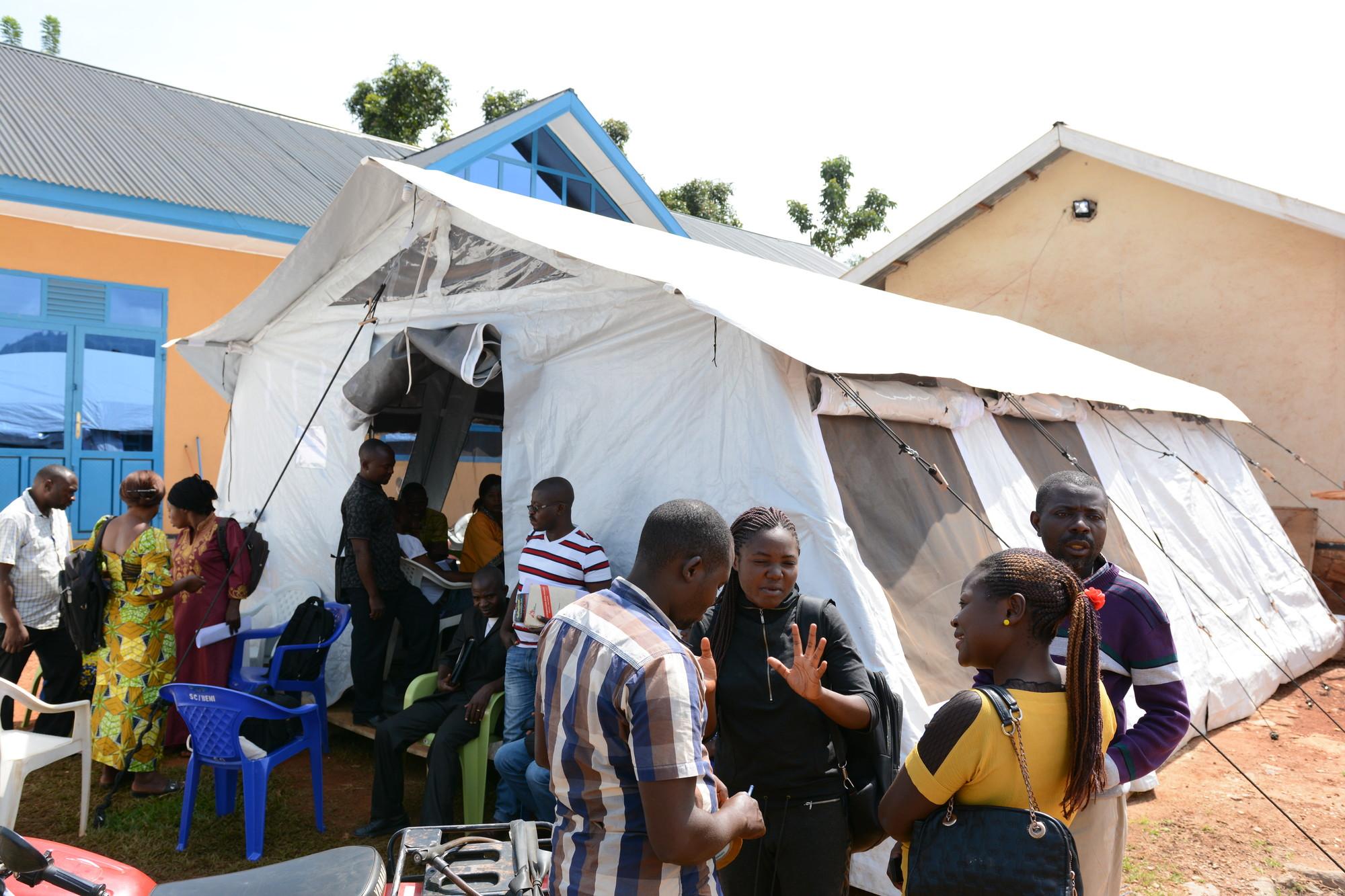 Um grupo de pessoas espera na fila em frente a uma tenda.