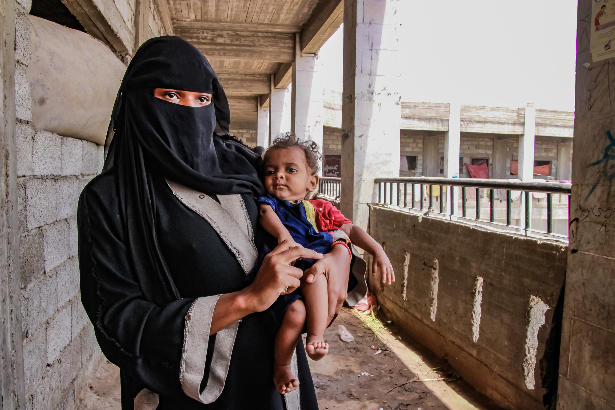A woman holds a baby while standing near a balcony.
