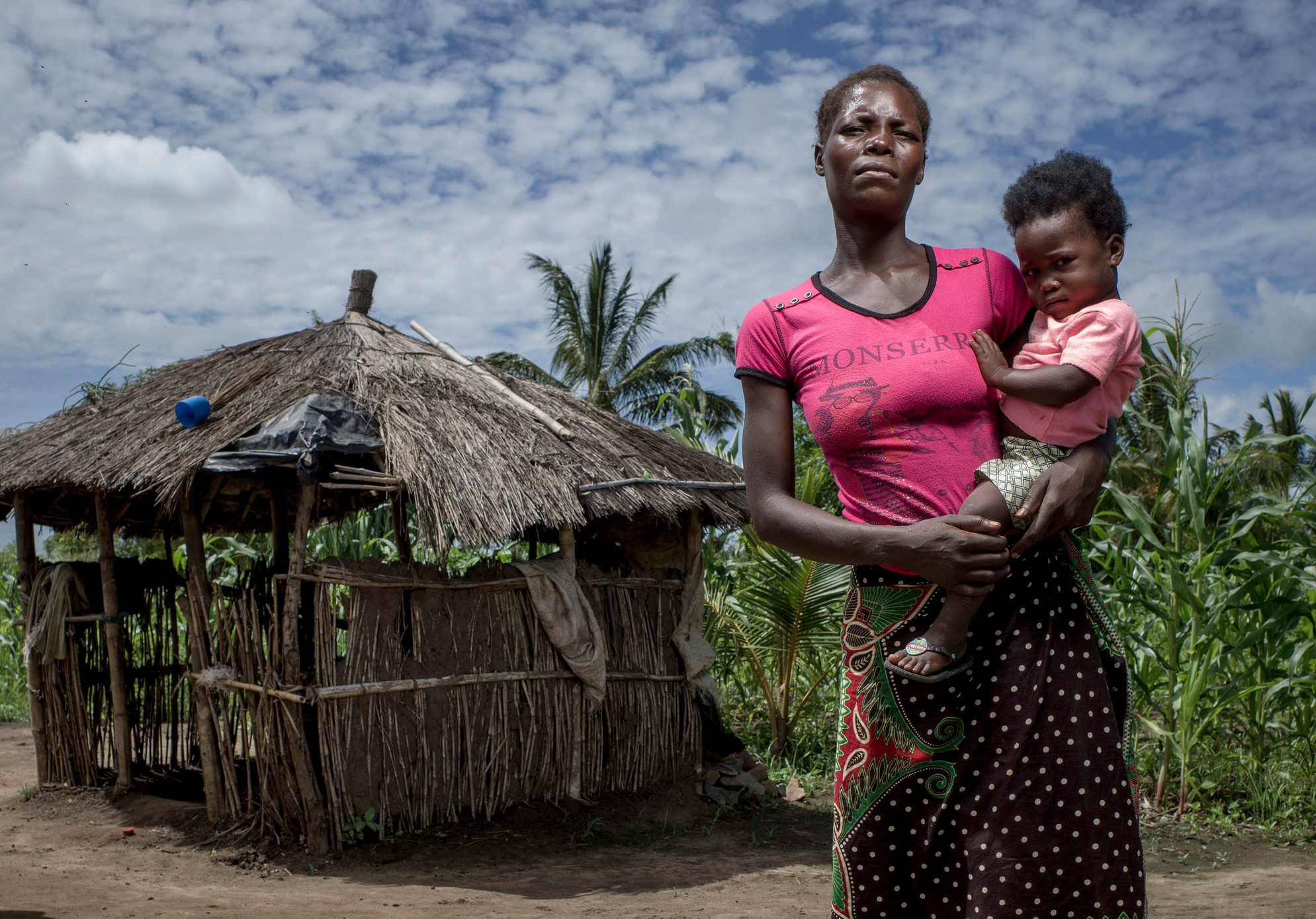 A woman holds her daughter in front of a wooden hut.