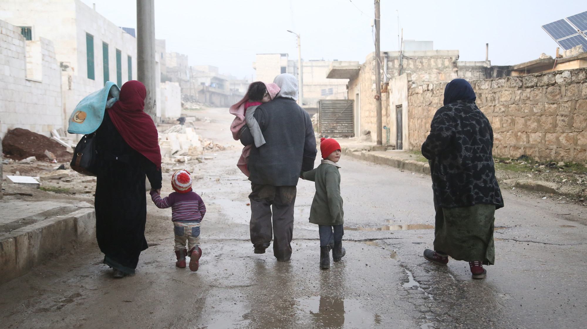 A group of children and adults walk in winter clothes in a bombed out city.
