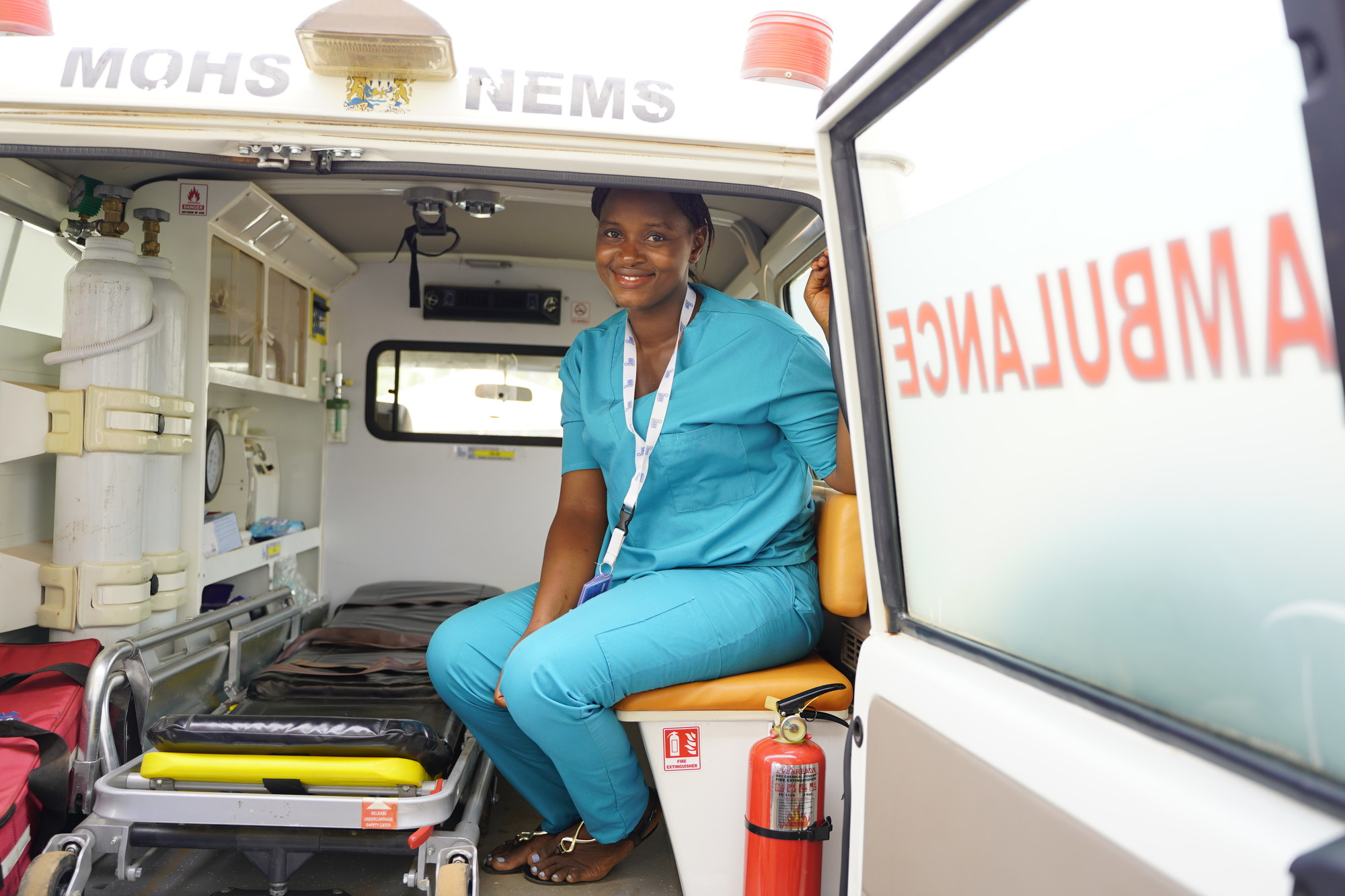 A female health care worker sits in the back of an ambulance.