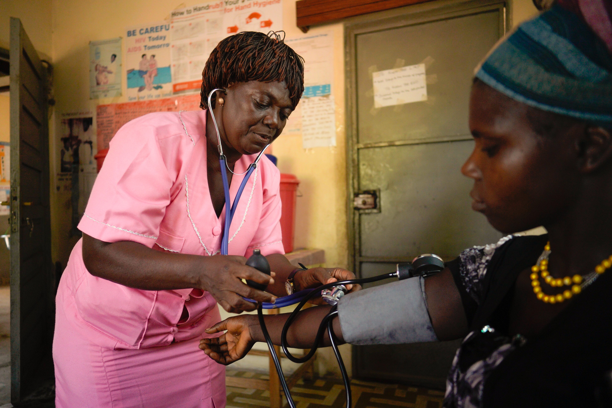 A female health care worker checks the blood pressure of a woman.