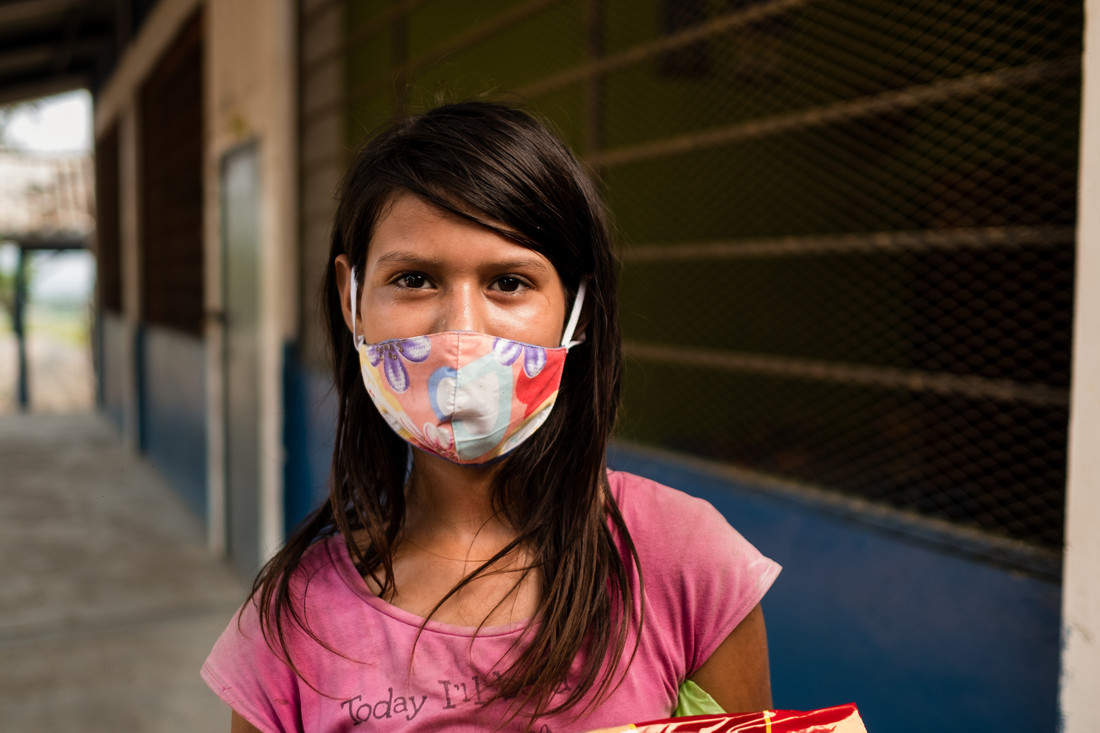 A portrait of a young Honduran woman wearing a floral facemask.