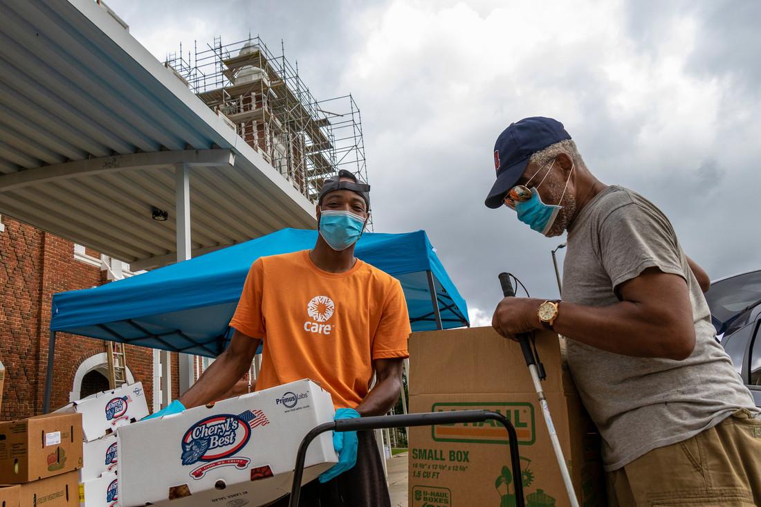 Un jeune homme portant un masque et des gants bleus et un t-shirt CARE orange porte une boîte en carton de fournitures. Un homme portant un masque bleu et tenant un bâton de marche se tient à côté.