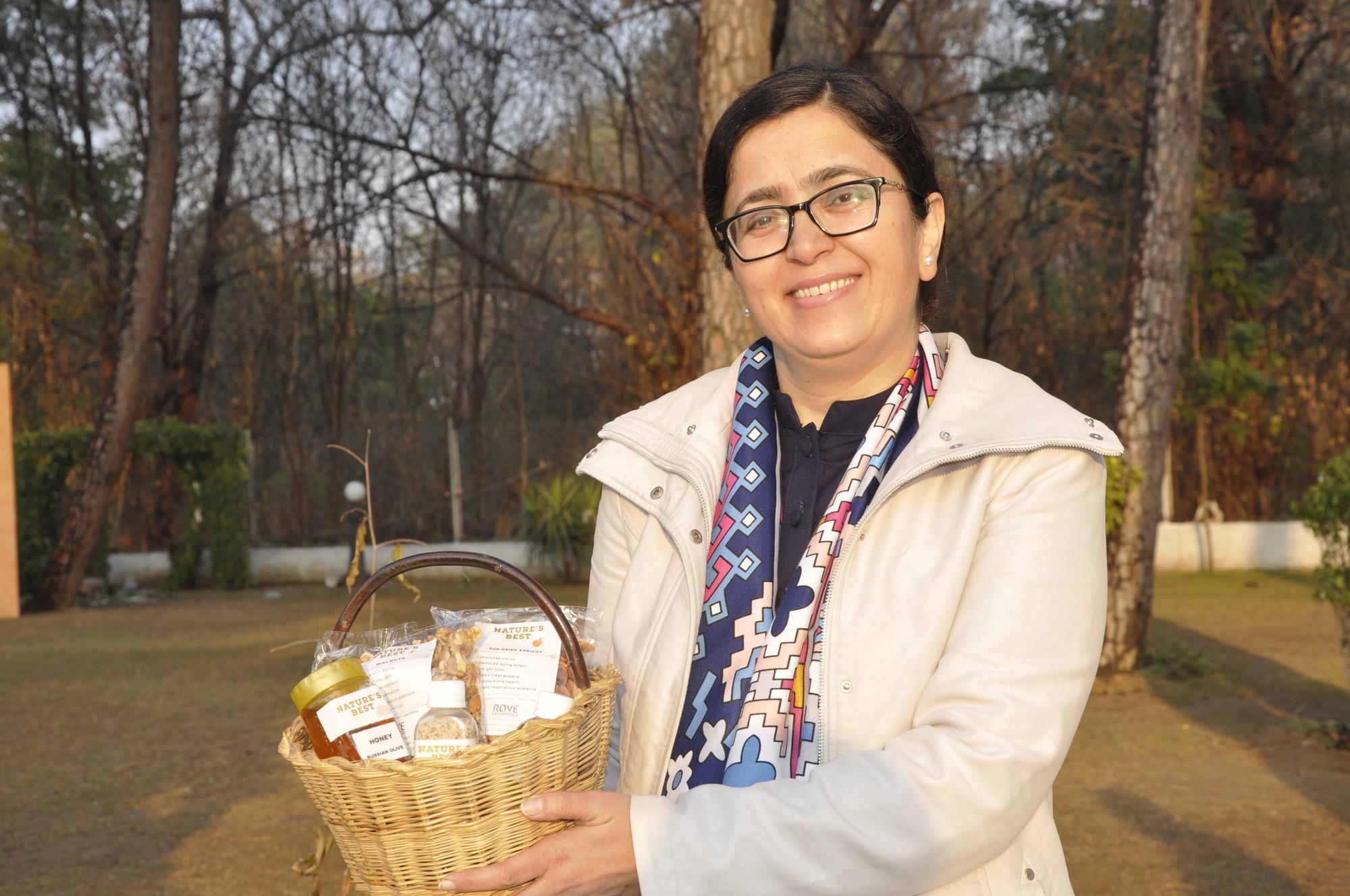 Una mujer sonríe mientras sostiene una canasta llena de pequeños obsequios.