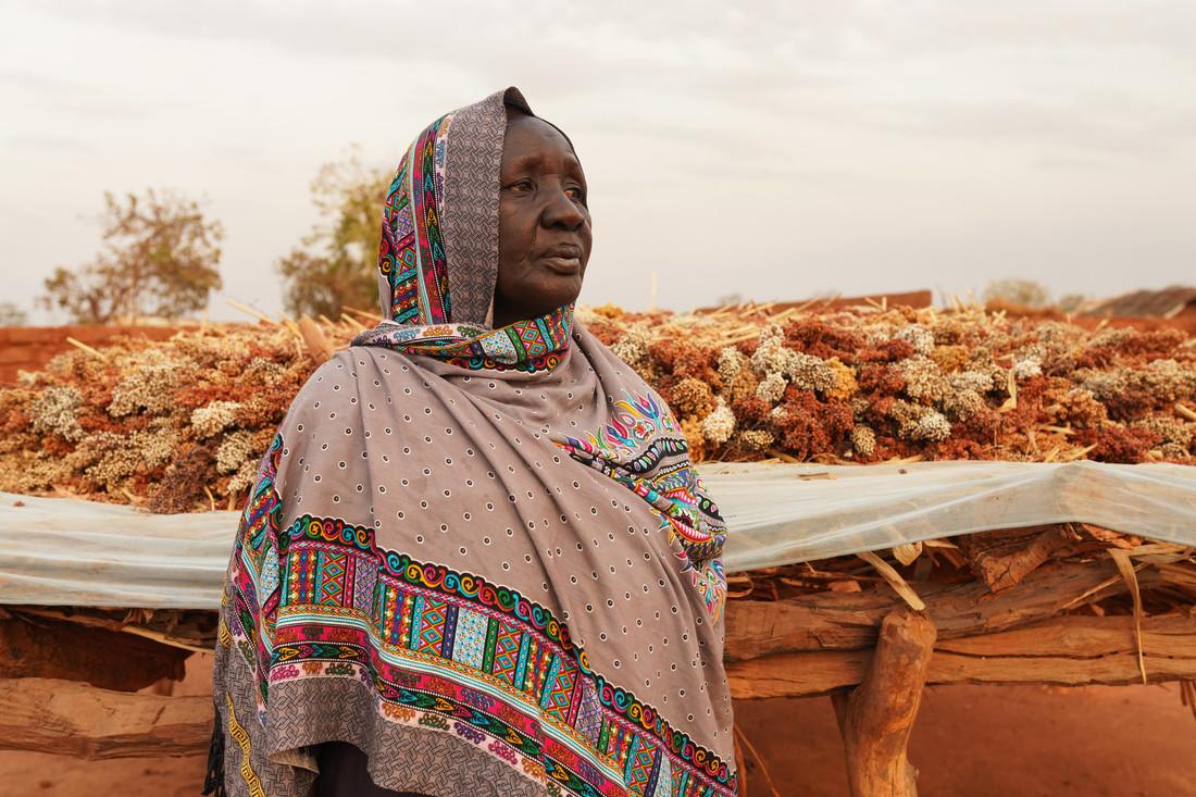 Uma mulher afetada pela crise humanitária do Sudão do Sul olha para o horizonte. Atrás dela, flores secas foram colocadas sobre uma lona branca.
