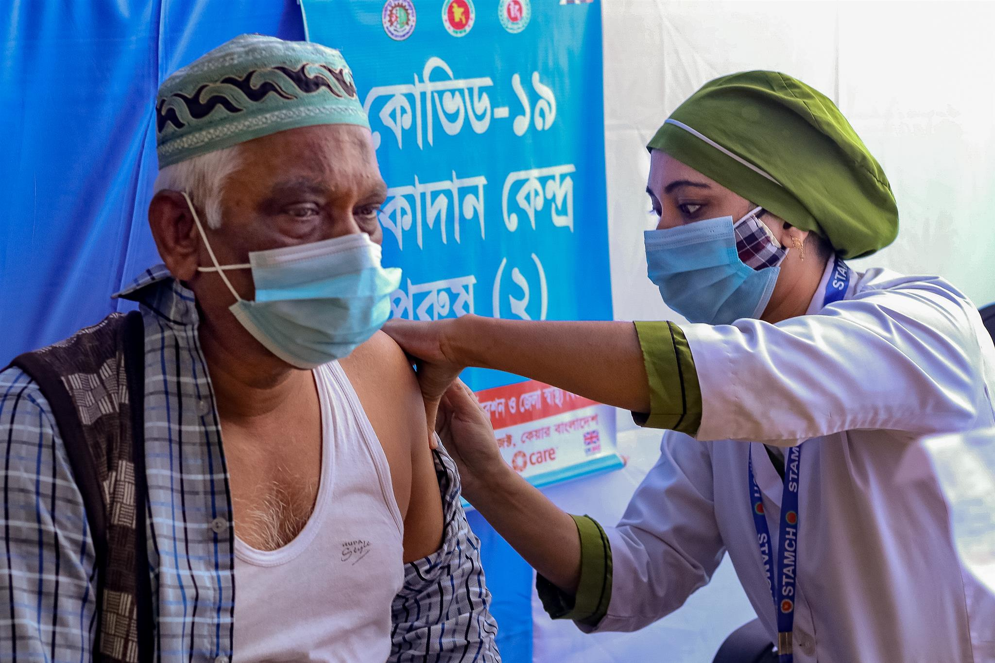 Both wearing masks, a woman health care worker gives a vaccine to a man.
