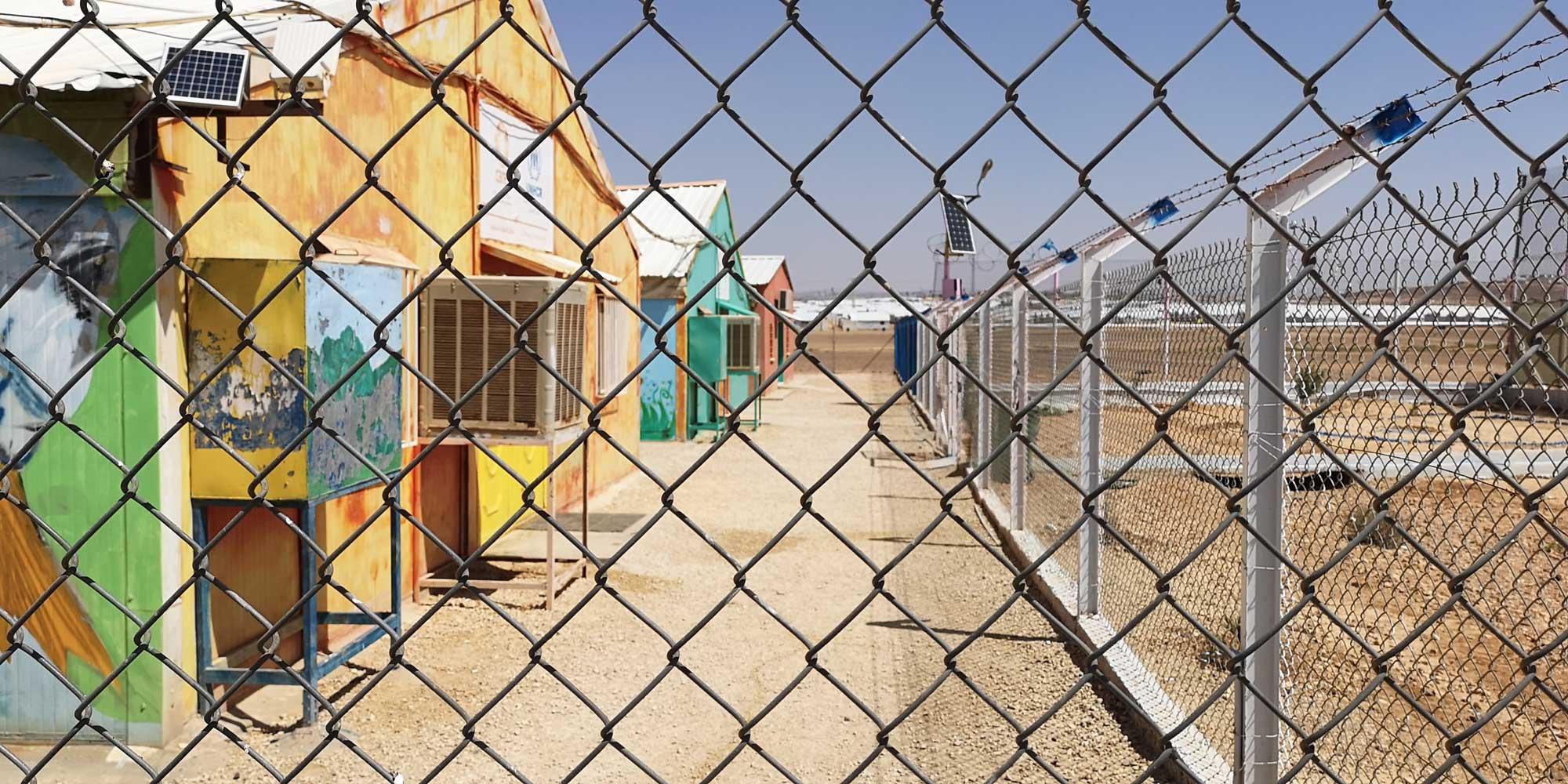 Edifícios atrás de uma cerca de arame em um campo de refugiados na Jordânia.