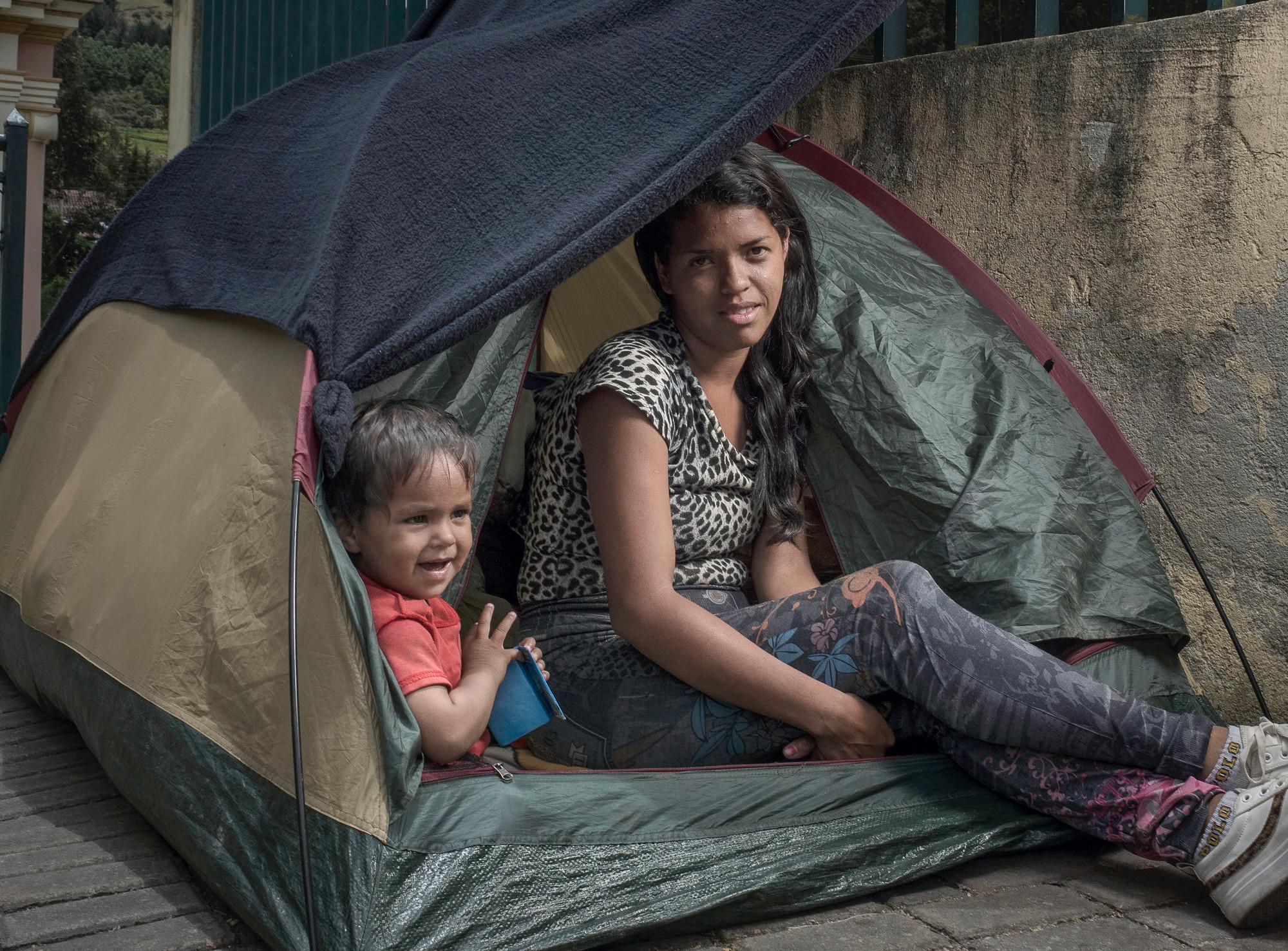 Une femme et un enfant sont assis dans une tente.