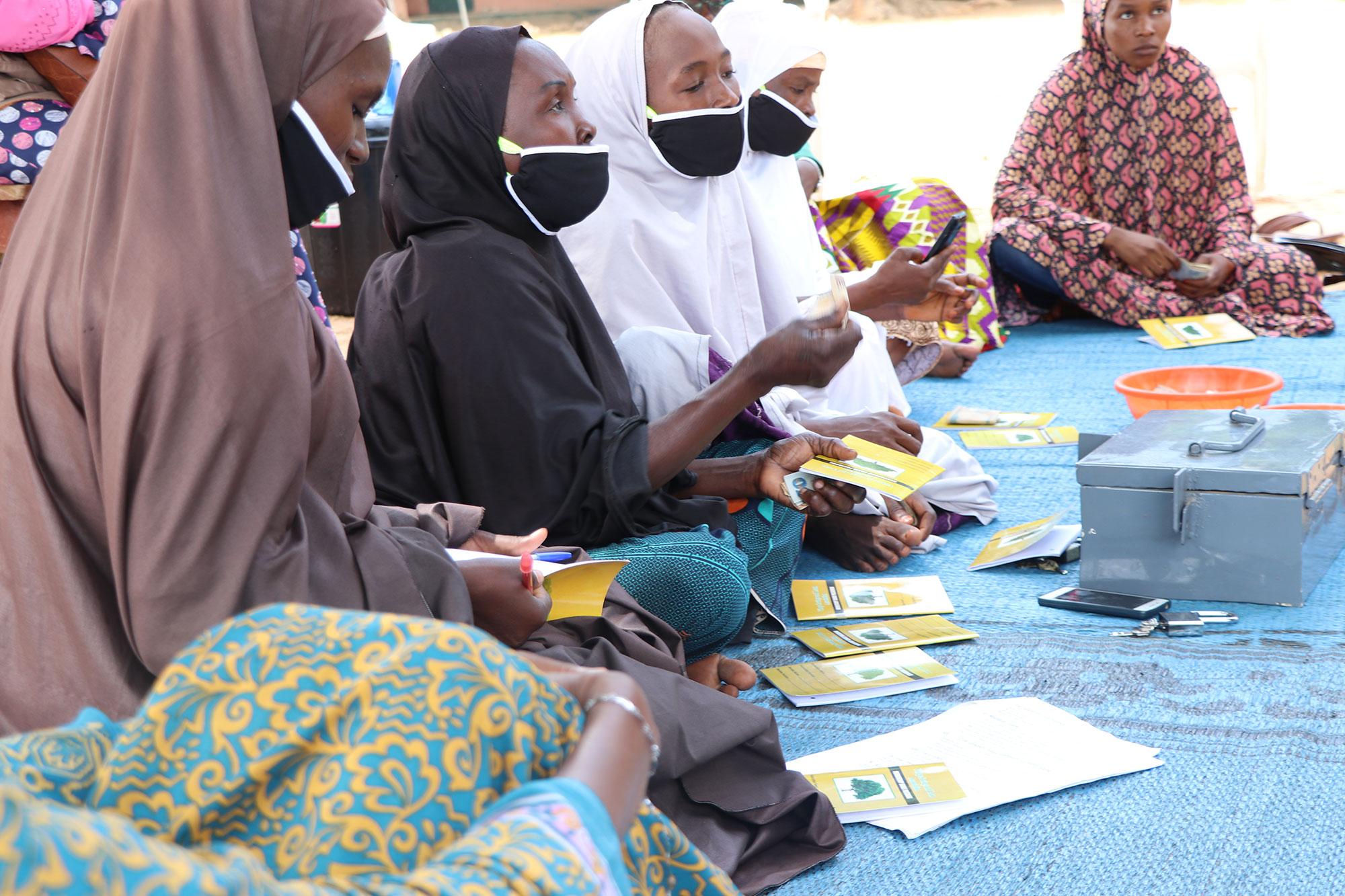 Mulheres mascaradas se reúnem em uma reunião da VSLA.