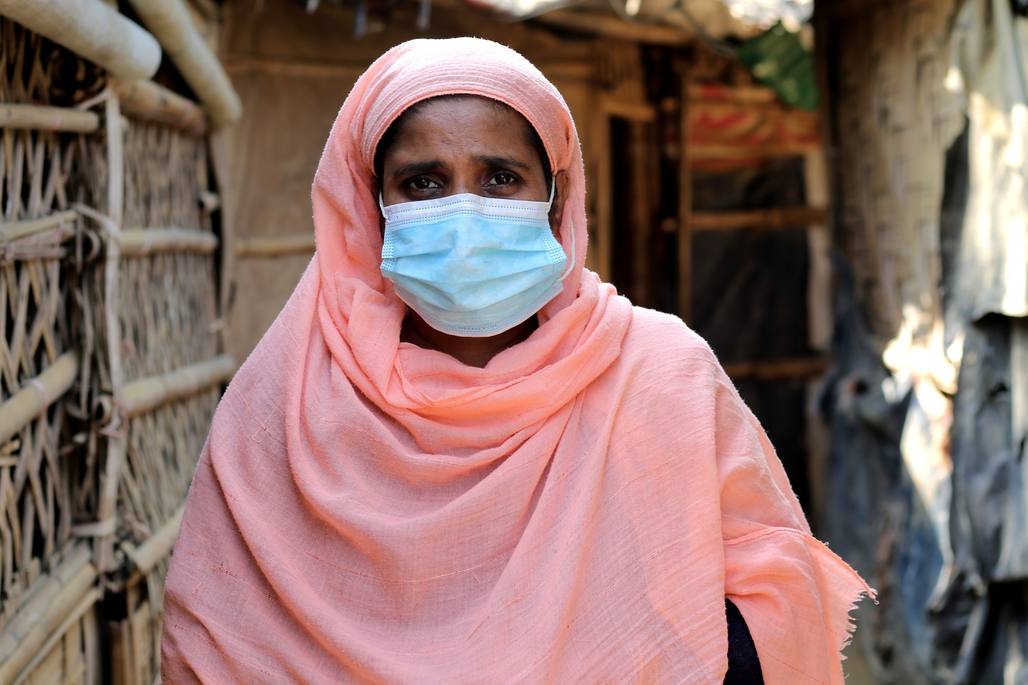A woman wears a surgical mask.