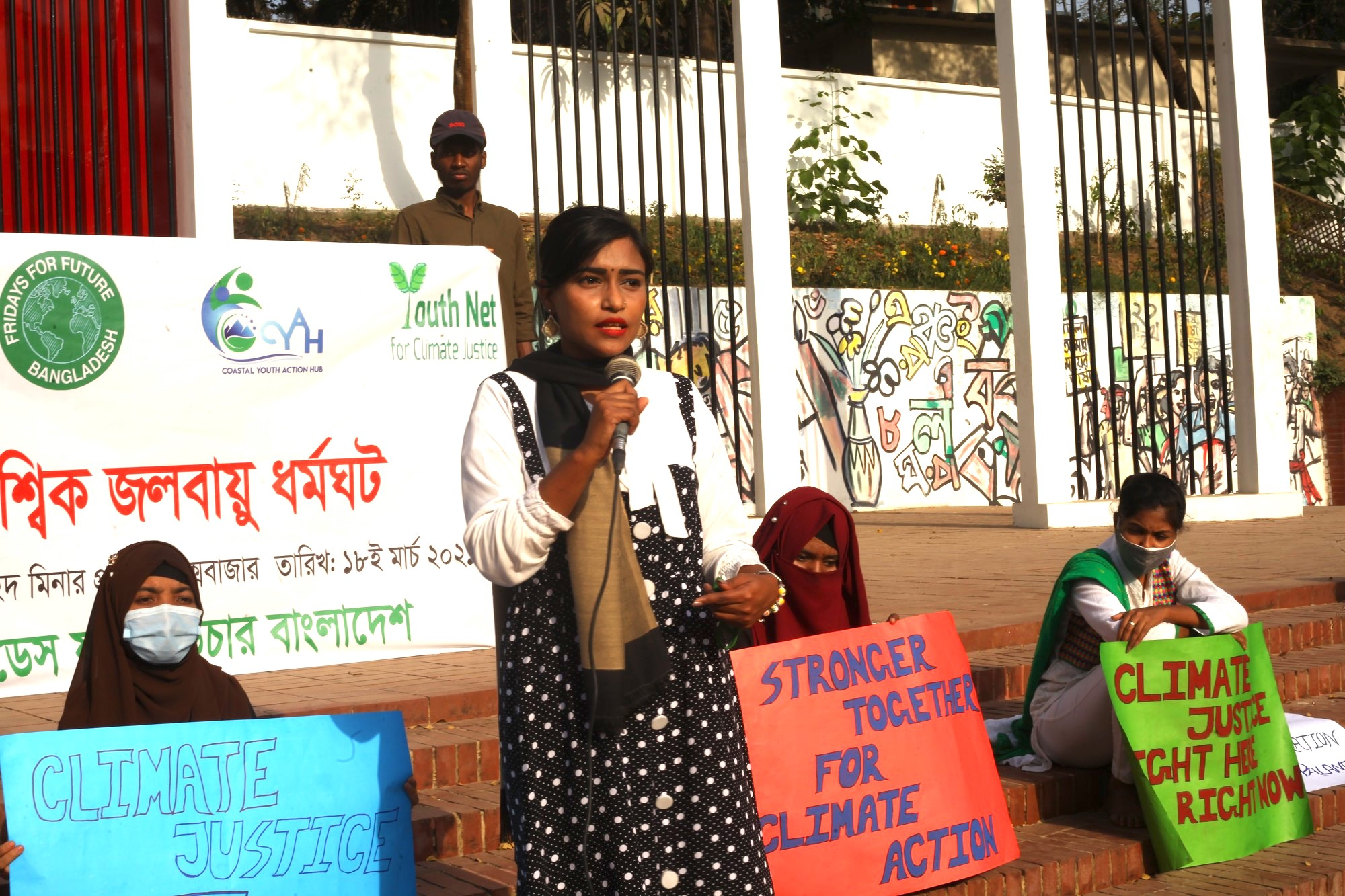 A woman holds a microphone at a climate justice event in Bangladesh.