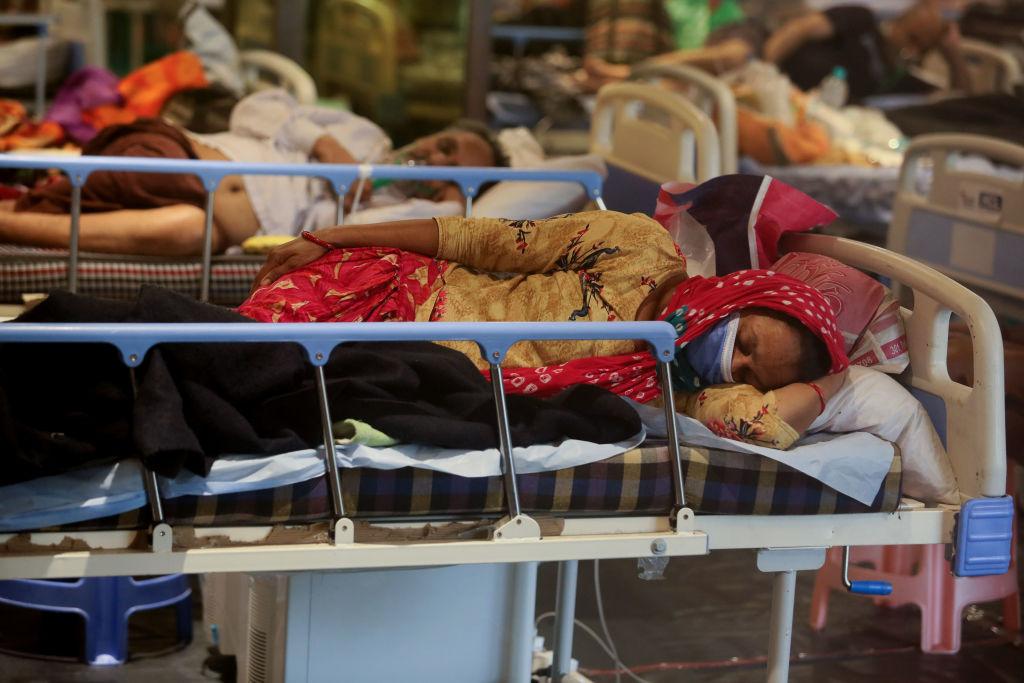 Una mujer india con una máscara azul descansa de costado en una cama de hospital. Detrás de ella, otros pacientes descansan en camas.