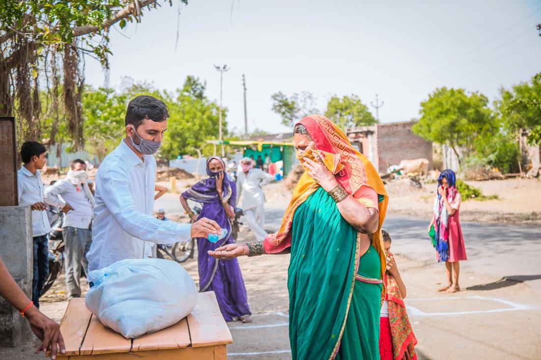 Un hombre dispensa desinfectante de manos en la mano de una mujer. Están afuera y ambos llevan máscaras. Detrás de ellos, otras personas están caminando, todas con máscaras.