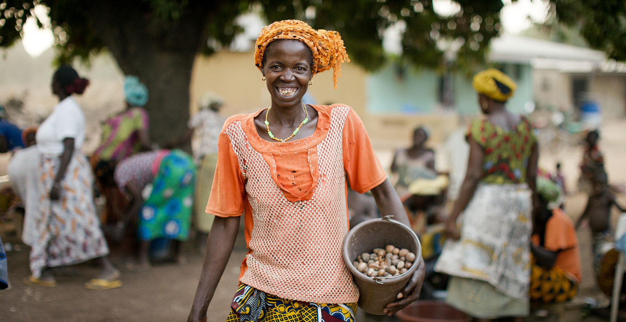 A woman holding a bucket smiles.