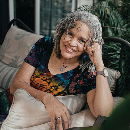 Charlayne Hunter-Gault smiles while sitting on a couch and resting her arms on the sidearm.