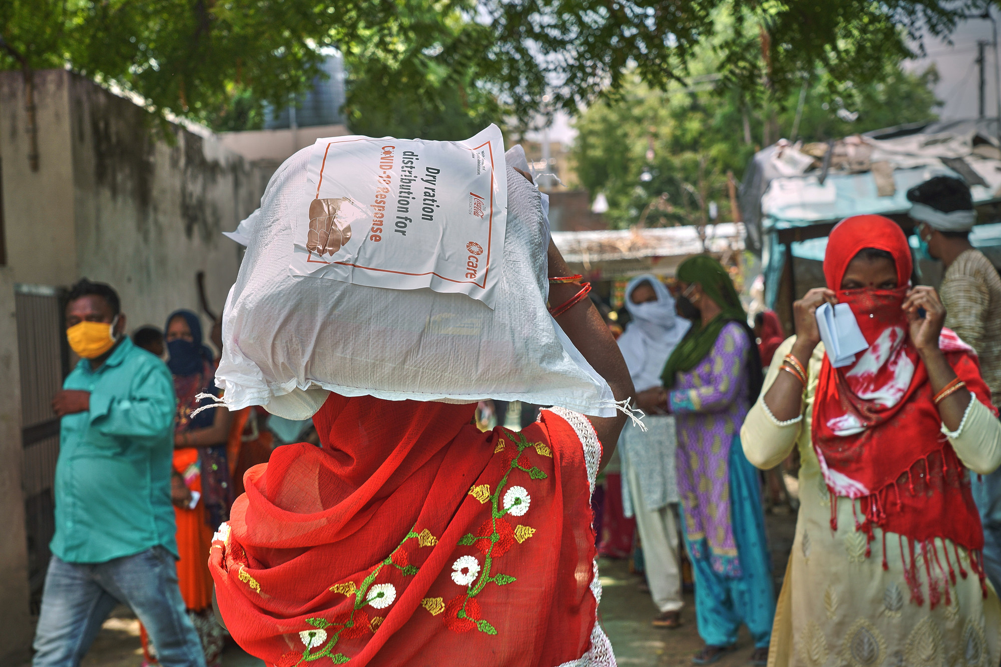 A woman carries a bag of supplies on her head.