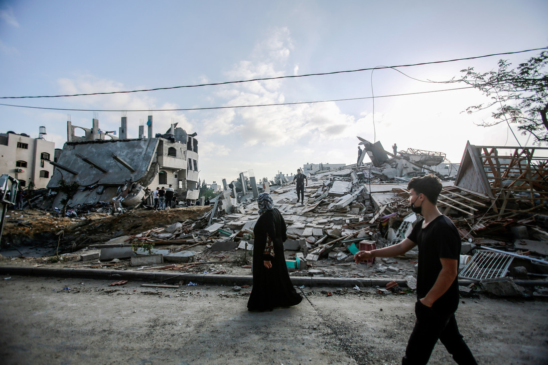 A woman wearing dark clothing walks by the ruins of a destroyed building.