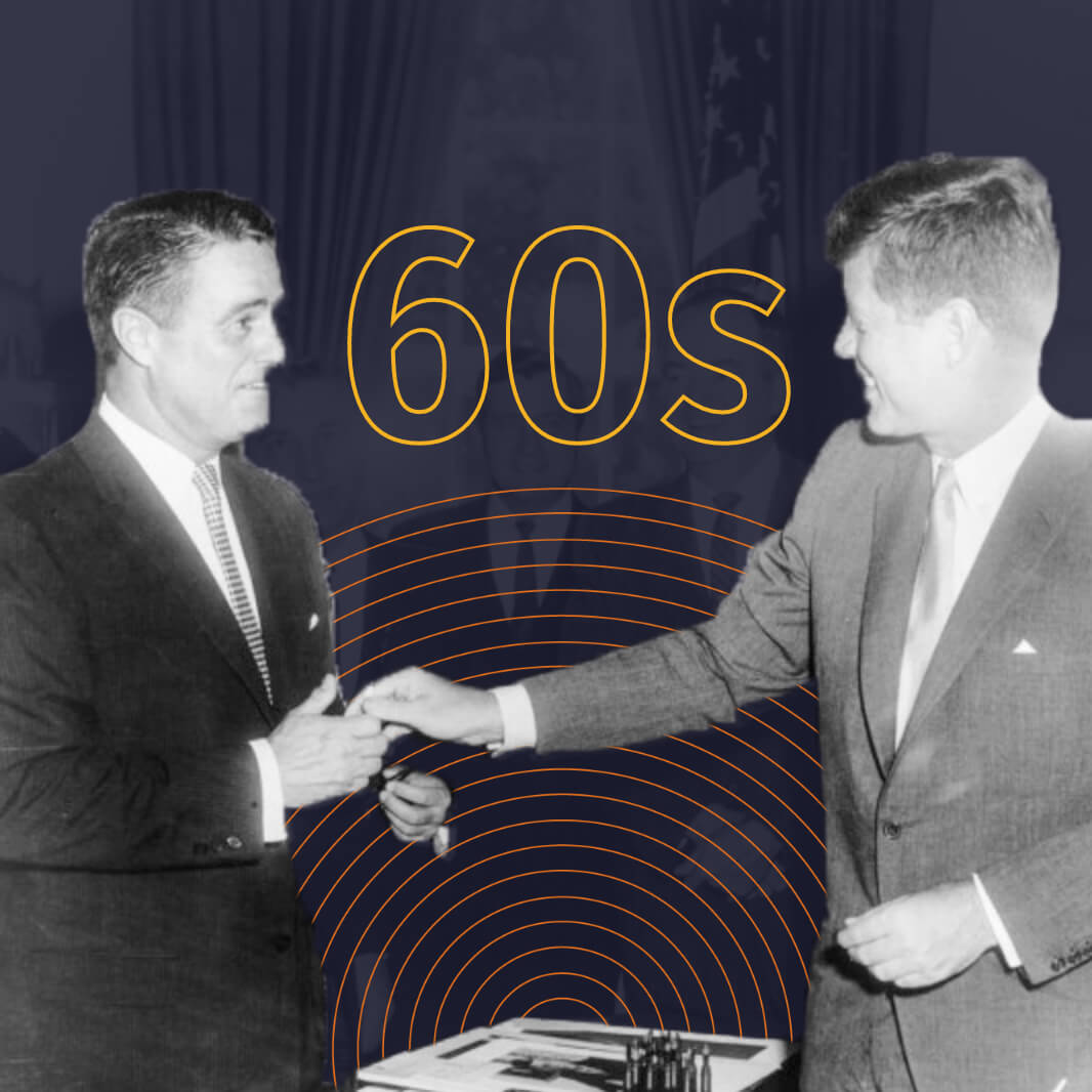 A black-and-white image of President John F. Kennedy shaking a man's hand. Behind them in yellow outlined text reads,