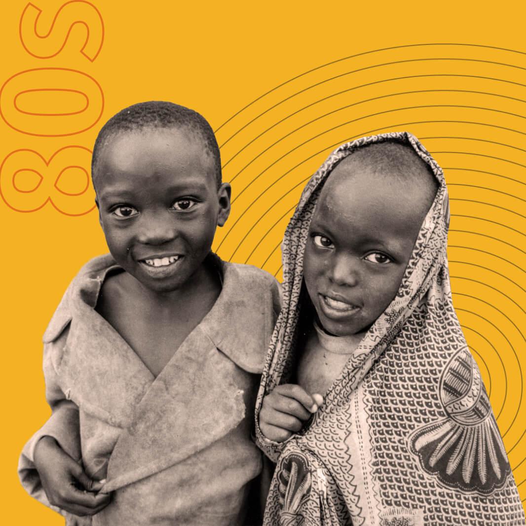 Uma imagem em preto e branco de duas crianças enroladas em roupas e cobertores.