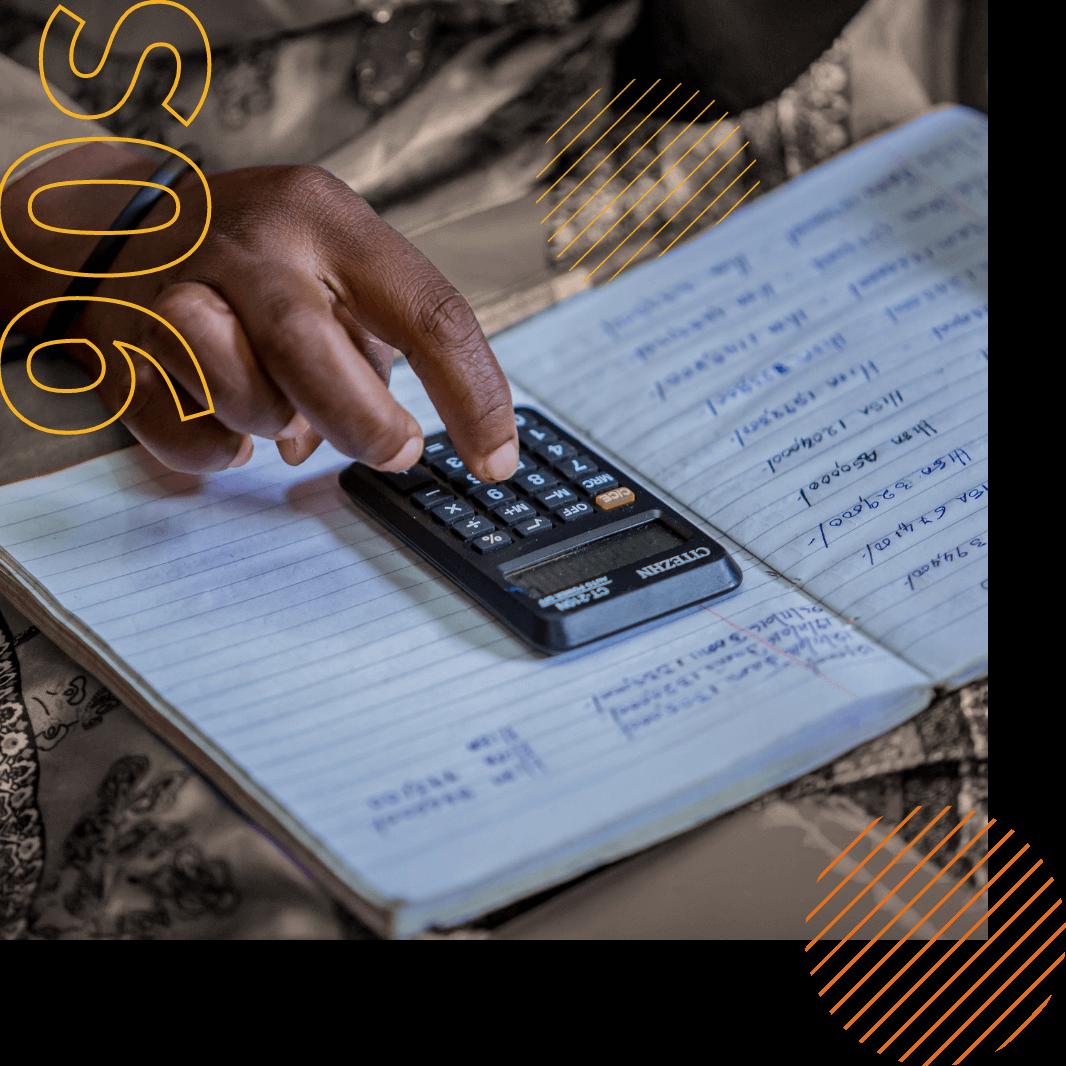 Uma imagem em close de uma pessoa digita números em uma calculadora, que está apoiada em um caderno.