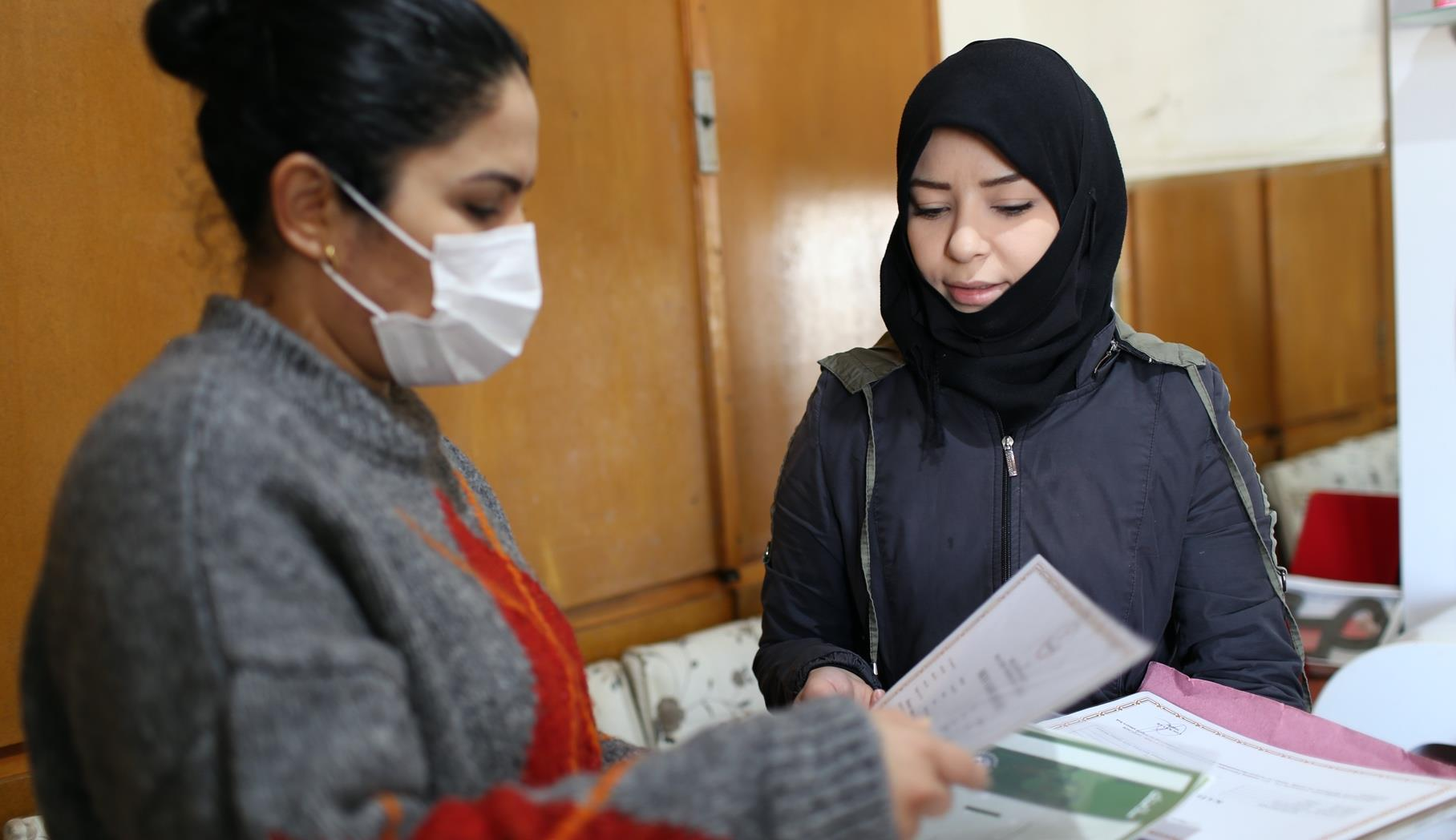 A woman wearing a black hijab approaches another woman, who is wearing a facemask and looking through papers.