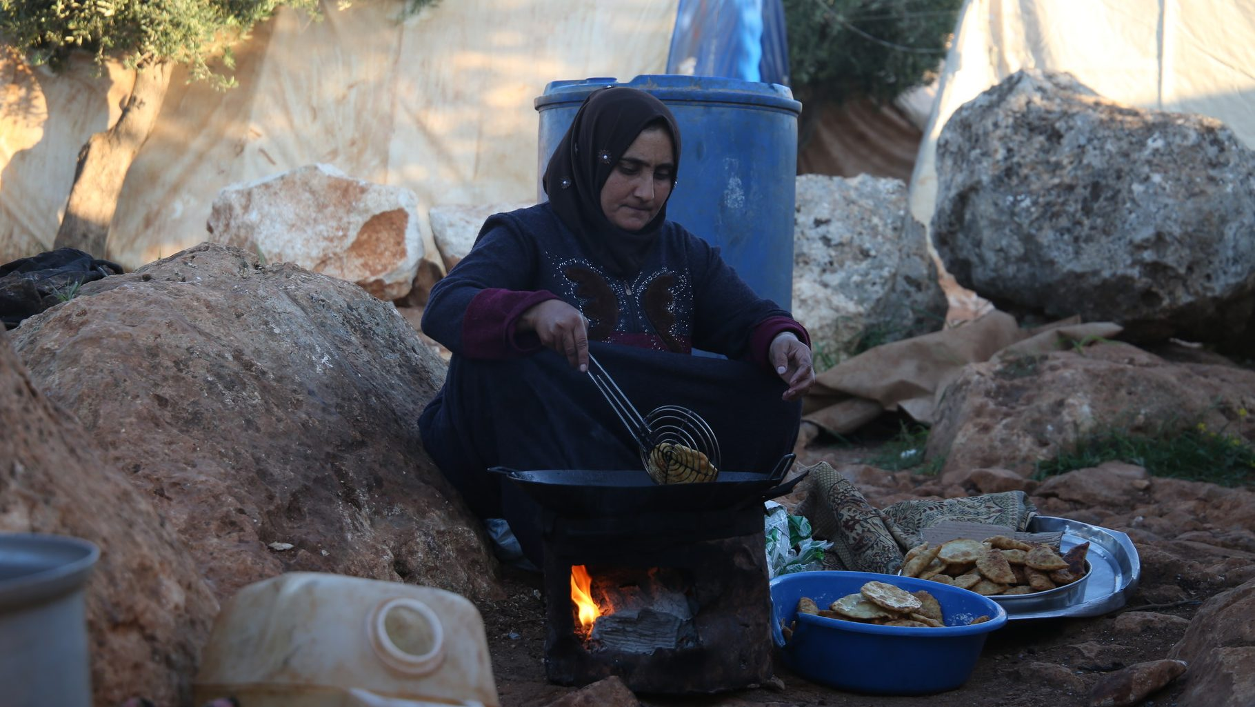 A Syrian woman in dark clothing cooks over an open fire in a displacement camp