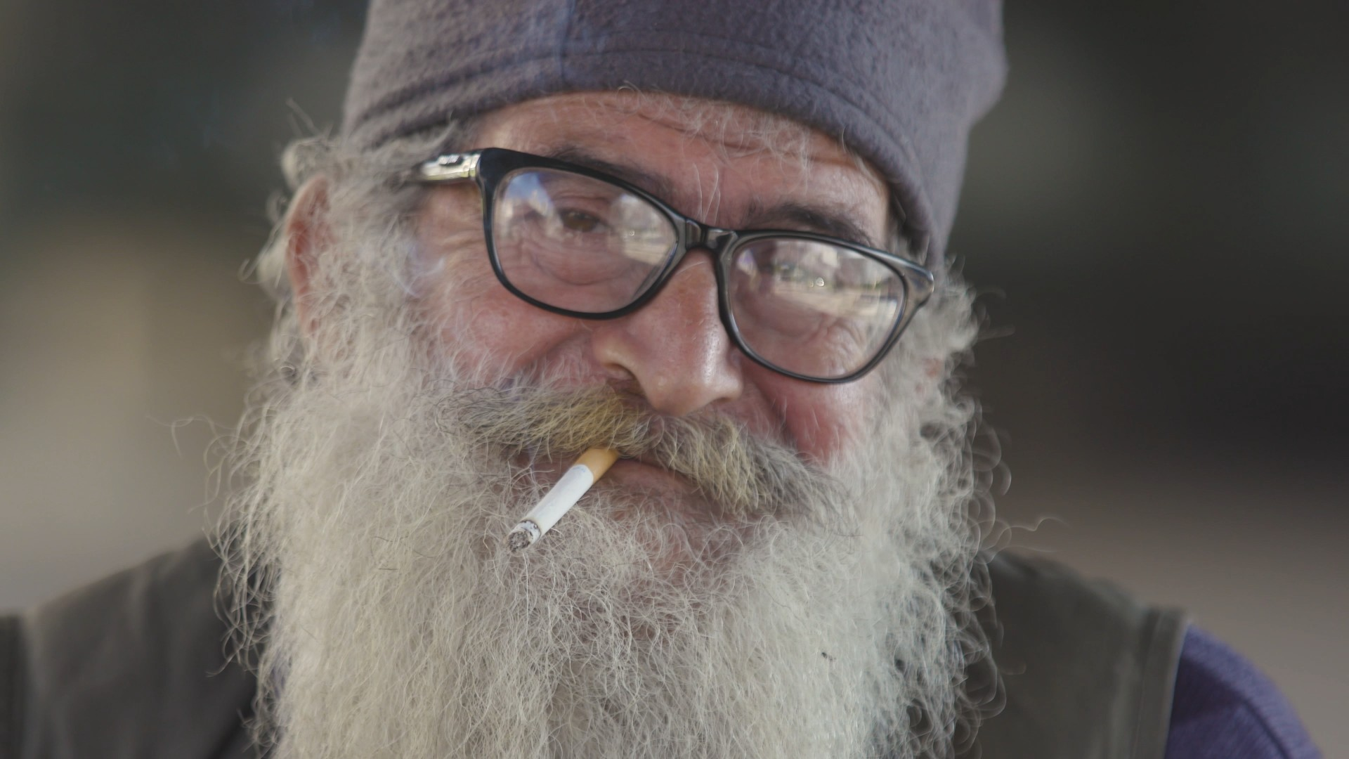 Close-up on an elderly Lebanese man with a thick grey beard as he smokes a cigarette