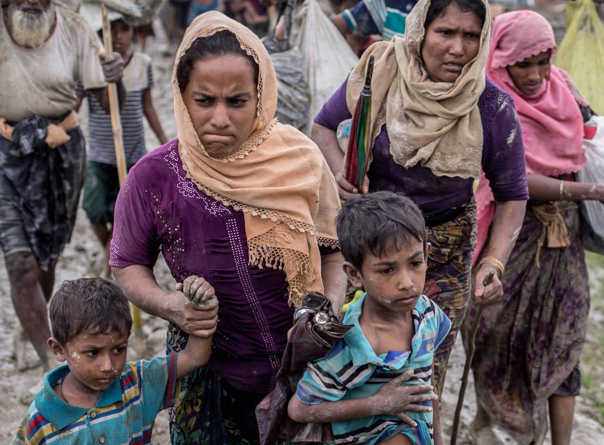 Una madre toma la mano de sus hijos remolcadores mientras camina por un camino embarrado.