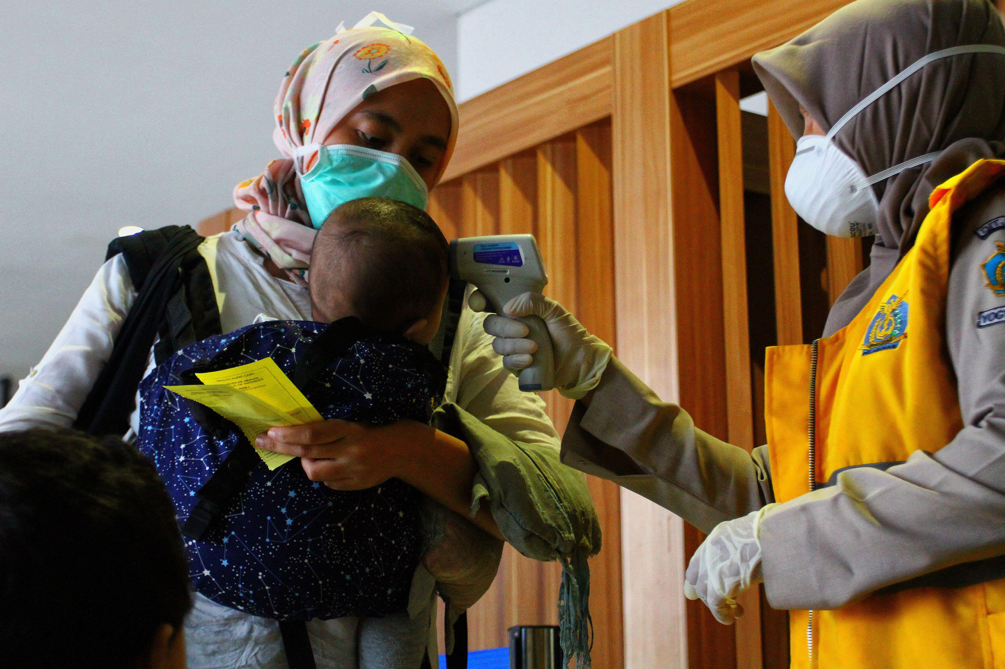 A woman in a surgical mask holds a baby while a healthcare worker checks the baby's temperature.