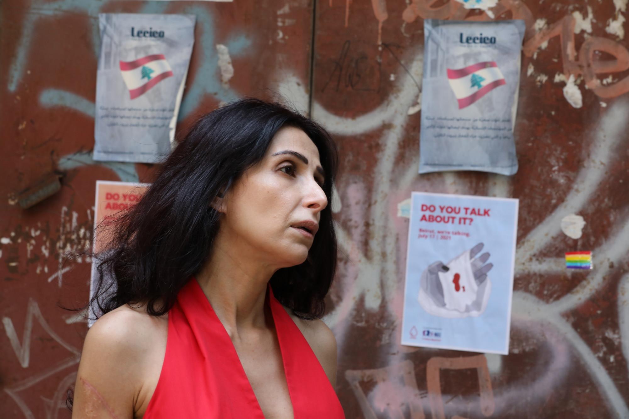 Une femme se tient devant un mur couvert de prospectus et de graffitis.