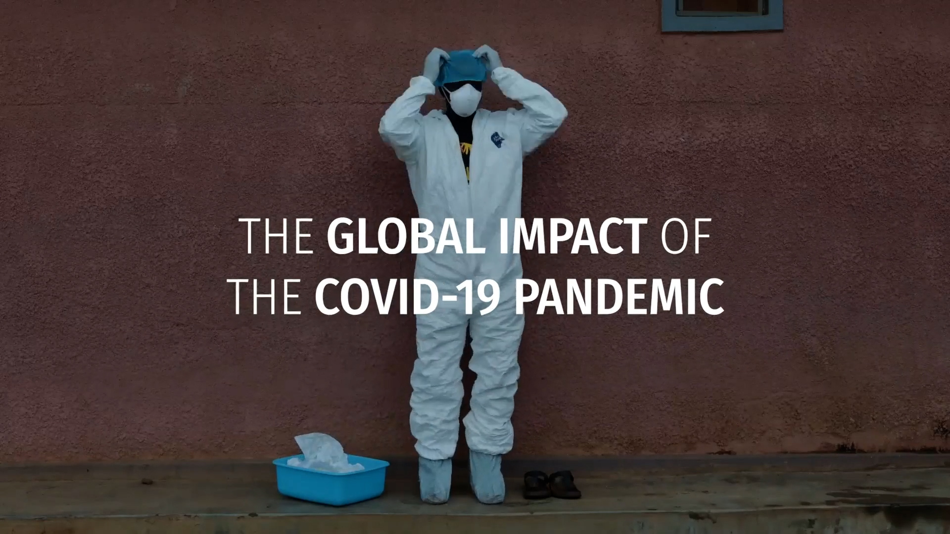 A screenshot of a video that shows a frontline health worker wearing a white suit and mask with light blue gloves and booties. Text is overlaid that says