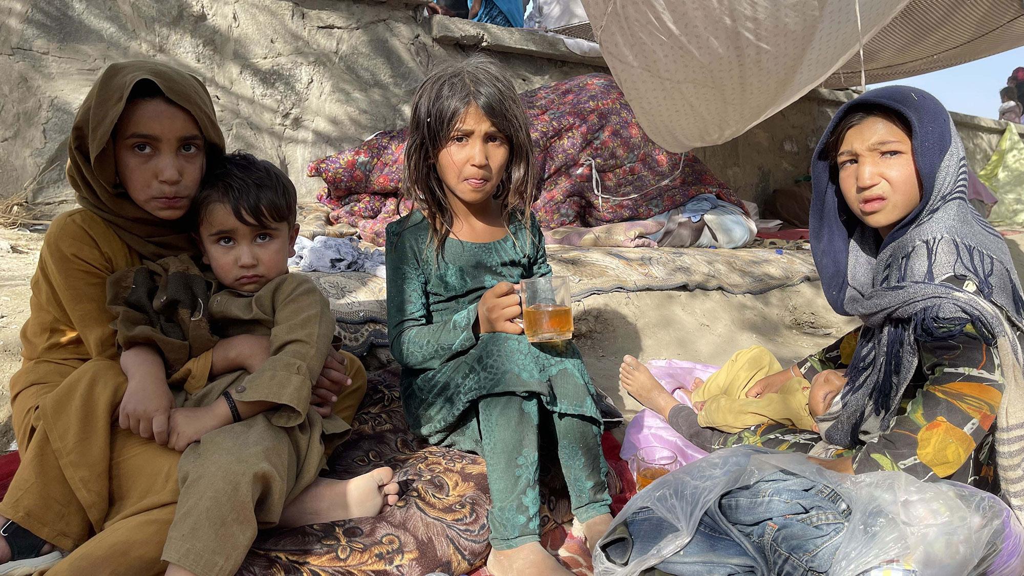 Des enfants afghans sont assis dehors.