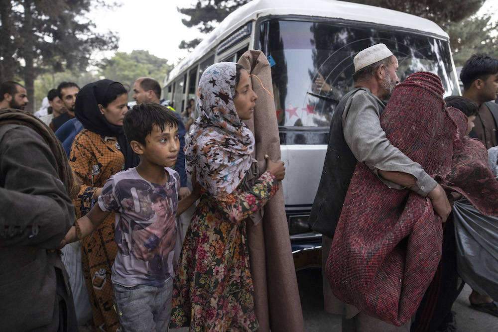 A group of people carry rugs, fabrics, and other items as they walk past a white van.