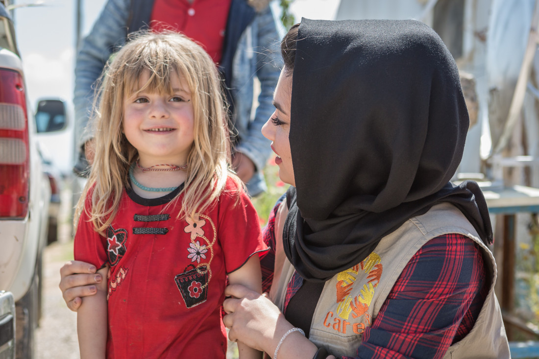 A CARE staff member wearing a tan vest and black headscarf kneels next to a young girl wearing a bright red shirt.