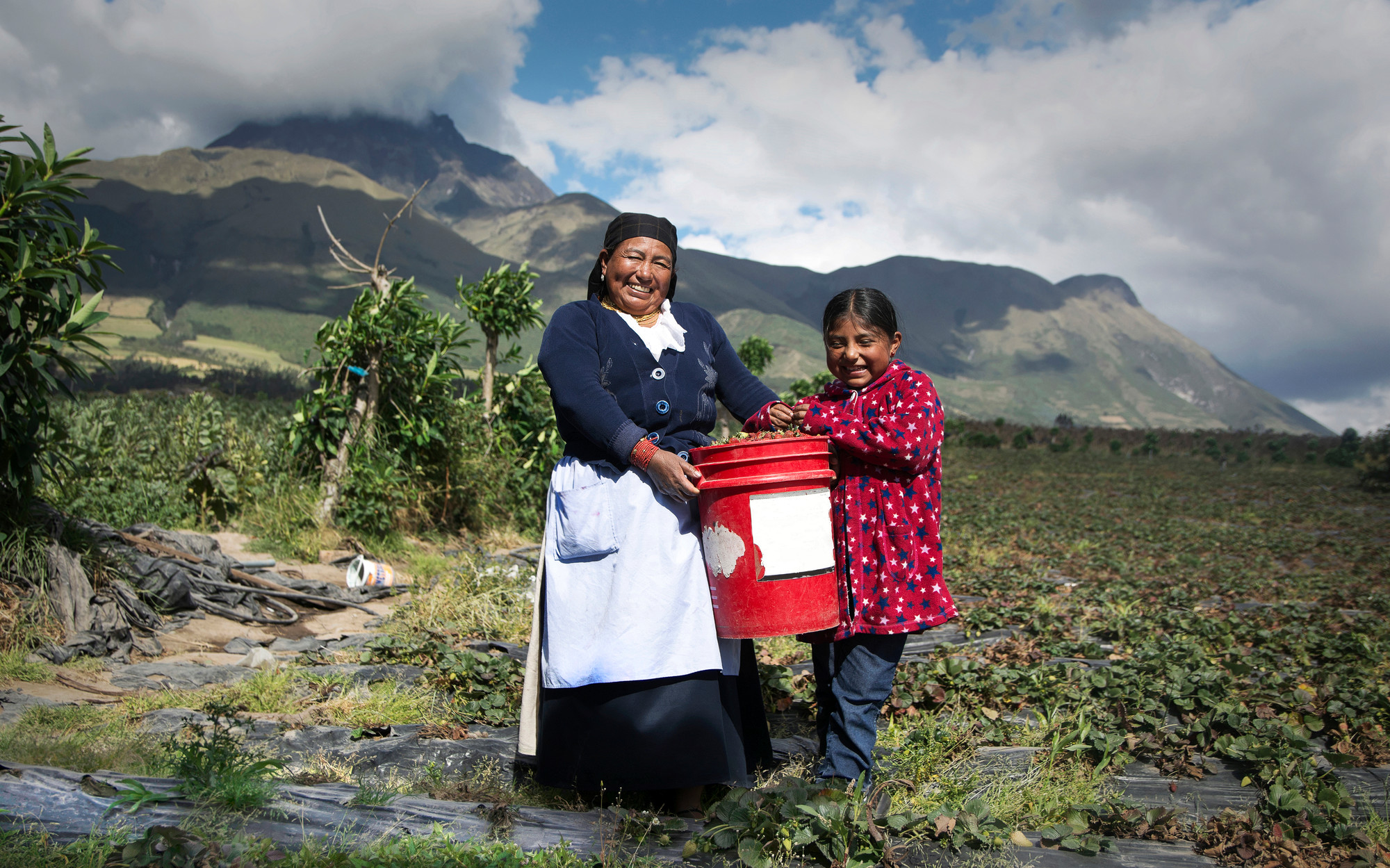 A mother and daughter stand in a field in Ecuador.