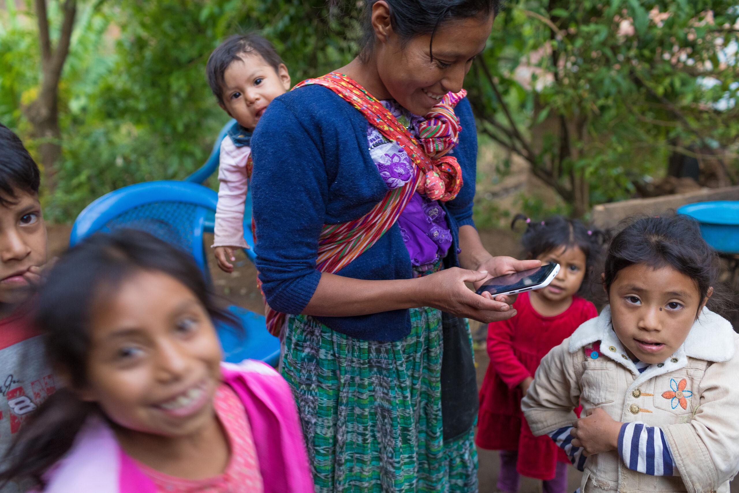 Une femme guatémaltèque sourit en envoyant des SMS sur un téléphone intelligent. Elle a un bébé sur le dos et trois enfants se tiennent autour d'elle.