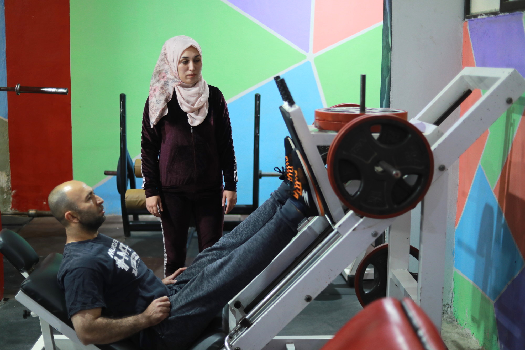 A man and a woman exercise in a gym