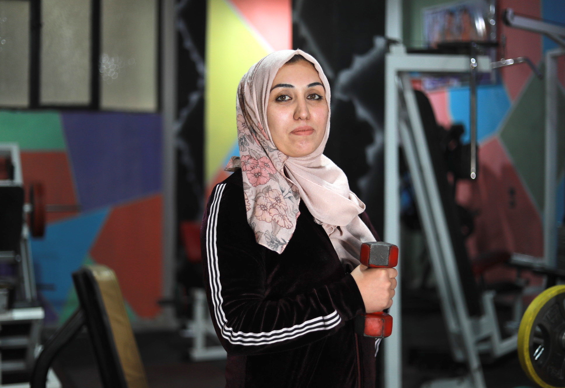 Woman holds a dumbbell in a gym.