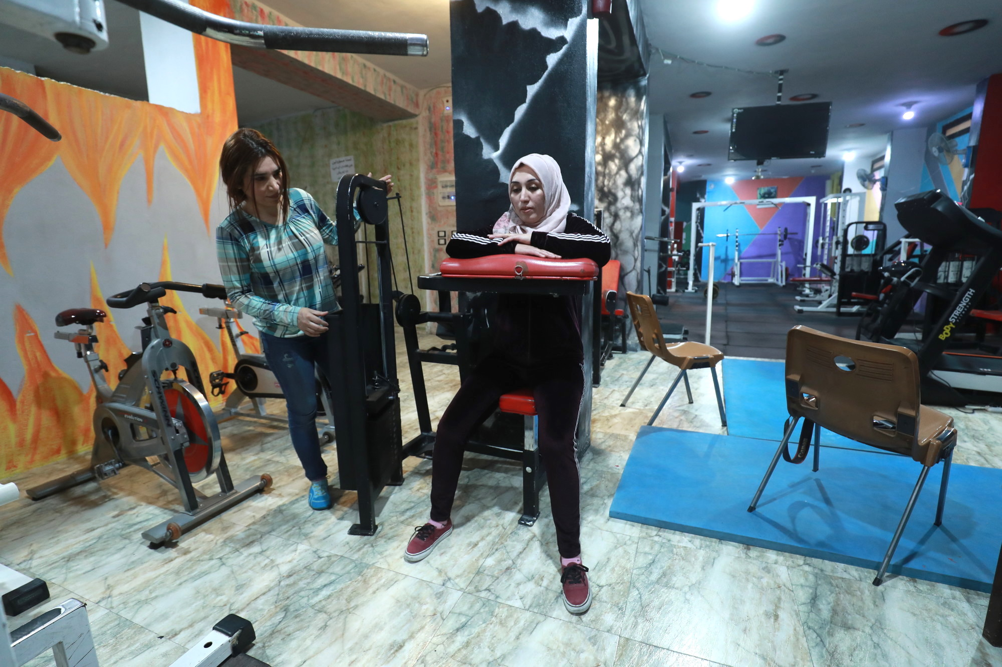 Woman exercises in a gym.