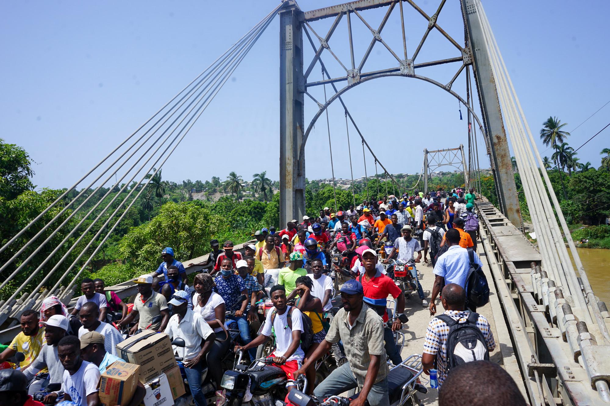 Des personnes photographiées sur et à proximité du pont Dumarsais Estimé, où les piétons et certains véhicules plus petits peuvent passer, mais pas les camions, fin août 2021, après un tremblement de terre de 7.2 qui a fait des ravages en Haïti. Le pont relie la ville de Jèrèmie au reste des autoroutes du pays.
