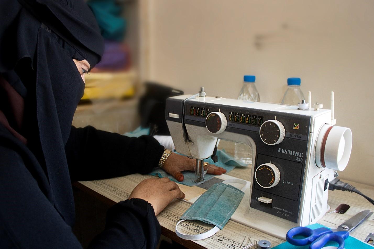 A Yemeni woman wearing a black veil sews a mask