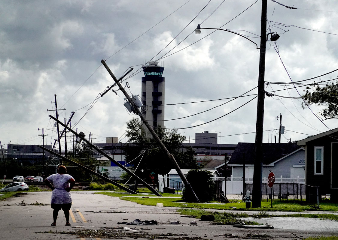 A woman stands on a street in Louisiana that has been damaged by Hurricane Ida. Multiple phone poles are down and there is debris in the street.